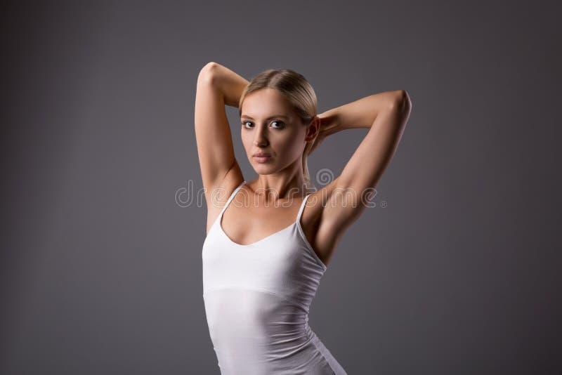 Ung tonårig kvinnlig skönhetstående med bullehänder upp på grå bakgrund arkivfoton