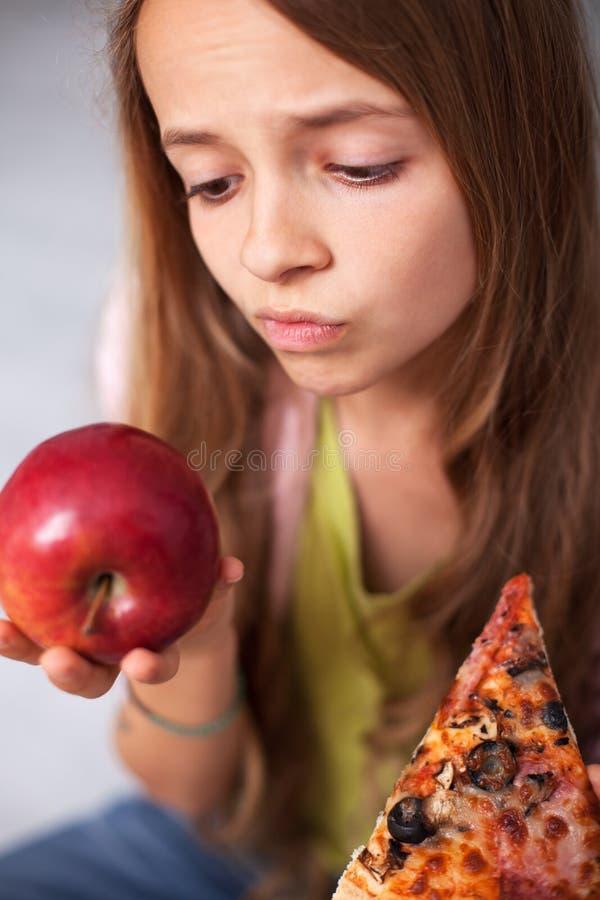 Ung tonåringflicka som är obeslutad mellan det sunda nya äpplet och ap fotografering för bildbyråer