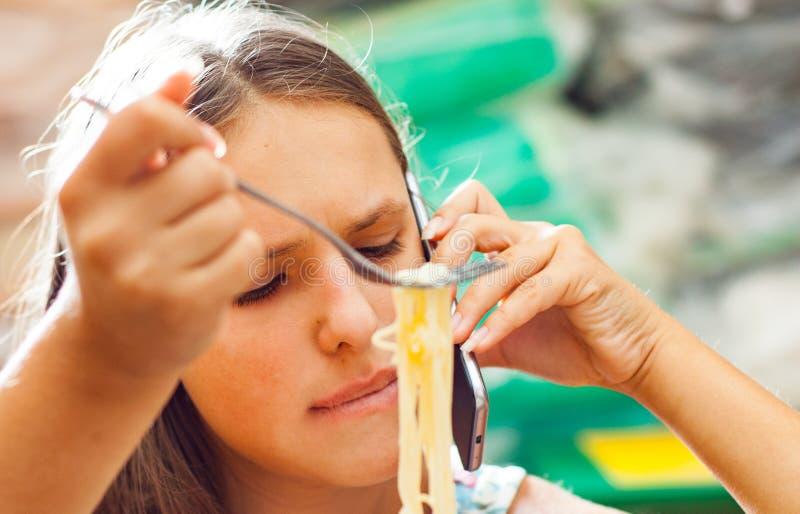 Ung tonåringflicka som äter spagettipasta och talar på telefonen arkivfoto