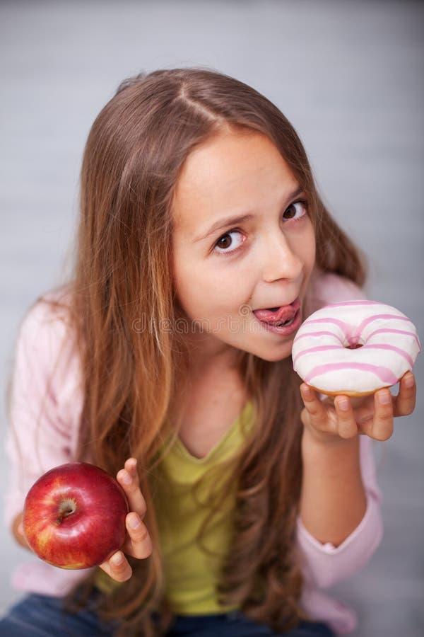 Ung tonåringflicka som frestas av den söta maten royaltyfri fotografi