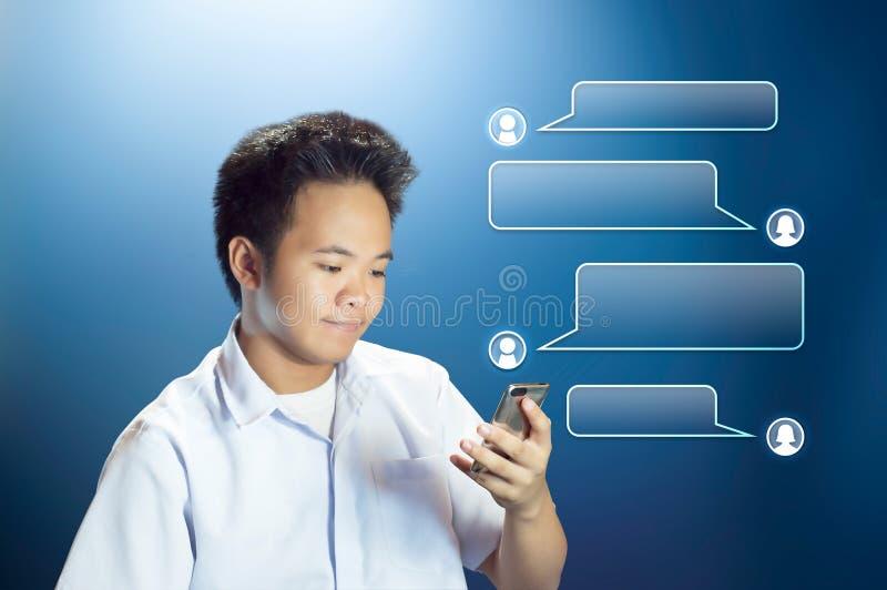 Ung tonåringstudent Texting som använder hans Smartphone med den projekterade konversationasken royaltyfri bild