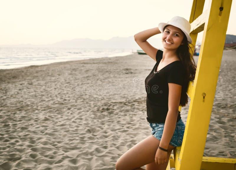 Ung tonårs- flicka på stranden på solnedgången arkivbild