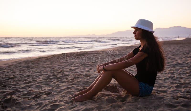 Ung tonårs- flicka på stranden på solnedgången royaltyfri bild