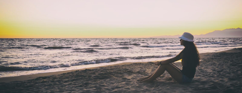 Ung tonårs- flicka på stranden på solnedgången royaltyfria bilder