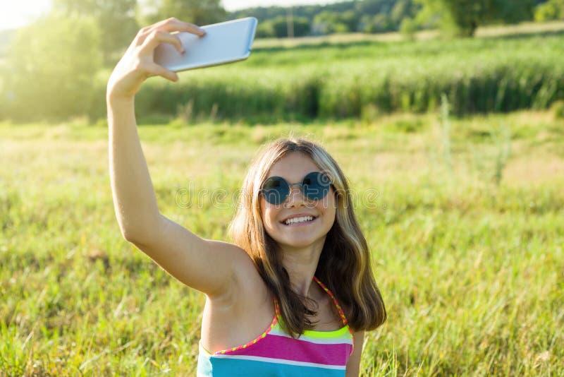 Ung tonårs- flicka som använder en smartphone som gör selfie i parkera royaltyfri foto