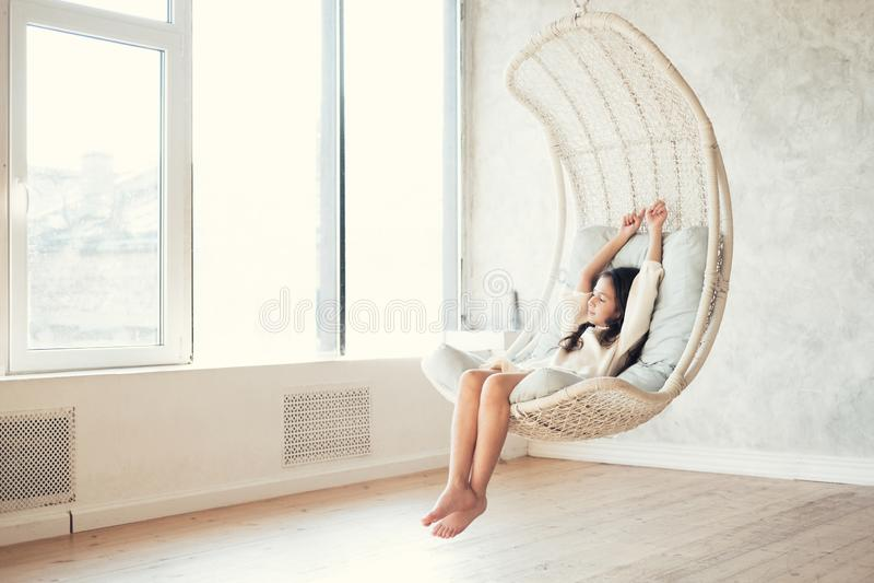 Ung tonårs- flicka som hemma kopplar av i bekväm hängande stol nära fönster Barnsammanträde i stol och kyla ut Koppla av concen arkivfoto
