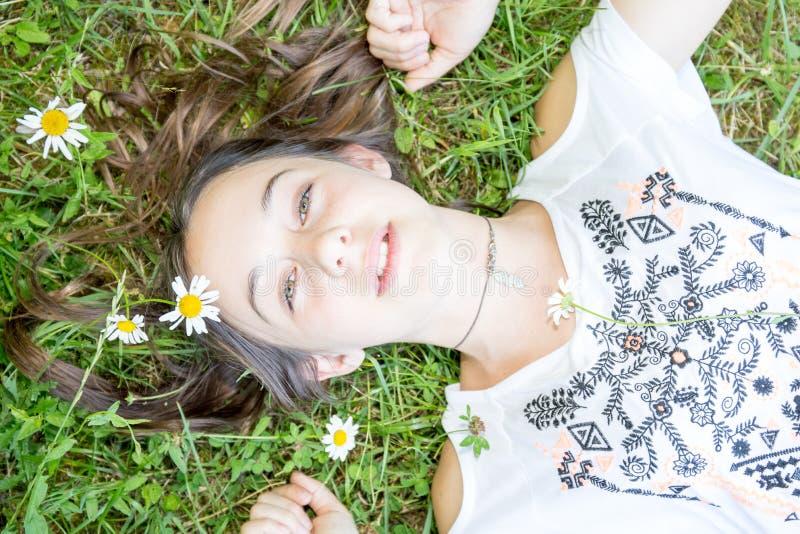 Ung tonårs- flicka som ligger i gräs och blommor med den sträckta handen royaltyfri fotografi