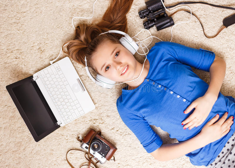 Ung tonårs- flicka som ligger på golvet med bärbara datorn royaltyfria foton