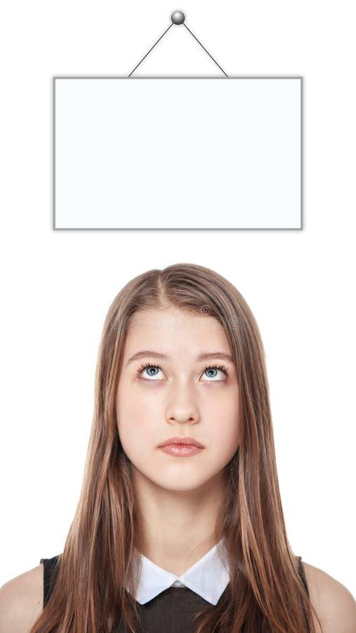 Ung tonårs- flicka som ser upp på tomma den isolerade bildramen royaltyfria foton