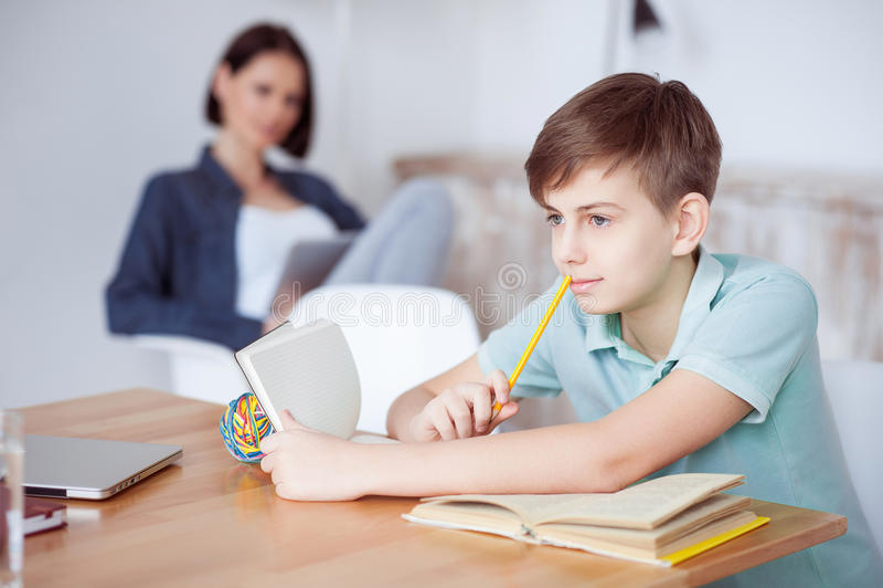 Ung tonårs- pojke som studerar på skrivbordet arkivfoton