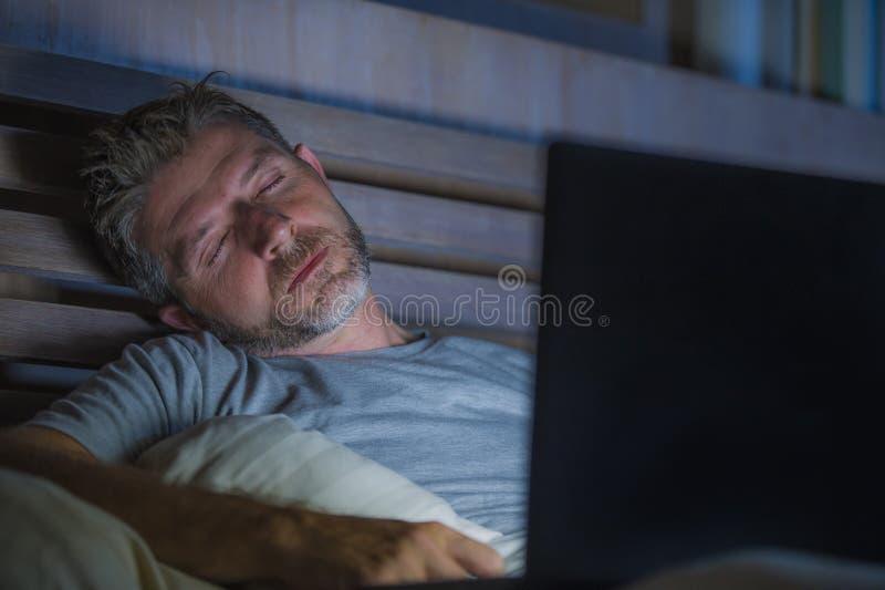 Ung trött och utmattad internet- eller arbetsknarkareman som sover, medan knyta kontakt sent - natt med bärbara datorn på säng i  arkivfoton