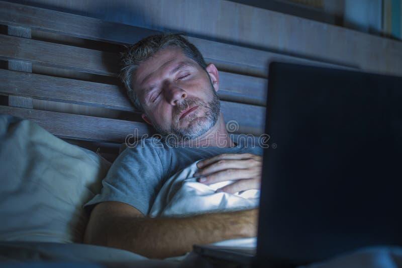 Ung trött och utmattad internet- eller arbetsknarkareman som sover, medan knyta kontakt sent - natt med bärbara datorn på säng i  arkivbilder