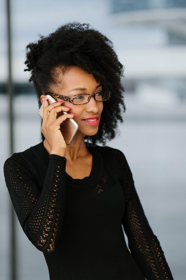 Ung trendig aff?rskvinna som anv?nder mobiltelefonen royaltyfri fotografi