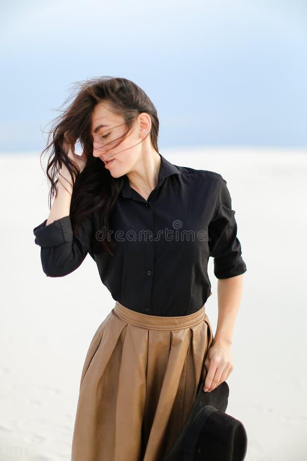 Ung trendig kvinna som bär den svarta blusen och brunt kjolanseende i vit bakgrund och håller hatten royaltyfria bilder