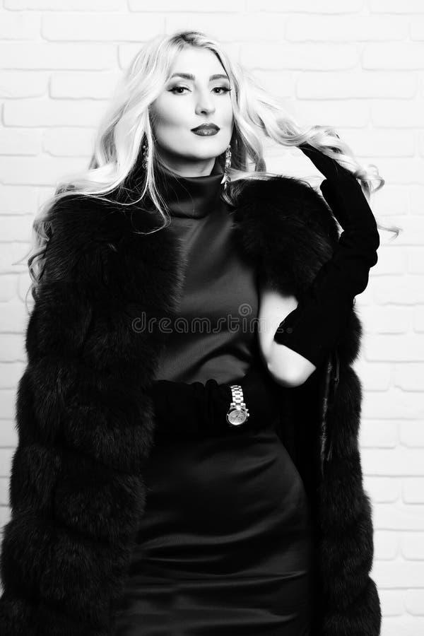 Ung trendig sexig nätt kvinna med härligt långt lockigt blont hår i midjalag av den burgundy päls och klänningen på royaltyfri foto