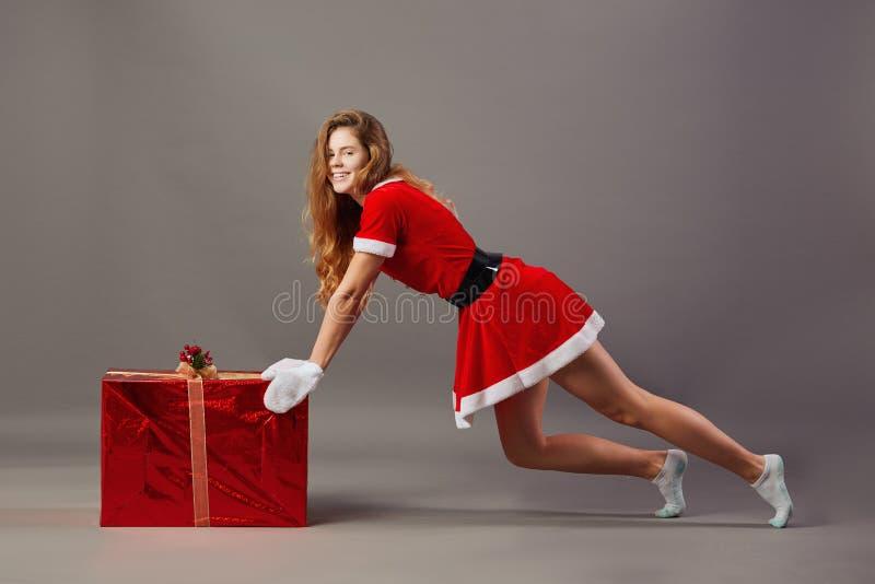Ung trevlig mrs Iklädda Santa Claus den röda ämbetsdräkten, de vita handskarna och de vita sockorna skjuter på den enorma julklap royaltyfri fotografi