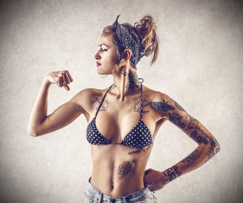 Ung tuff kvinna med tatueringar royaltyfri bild