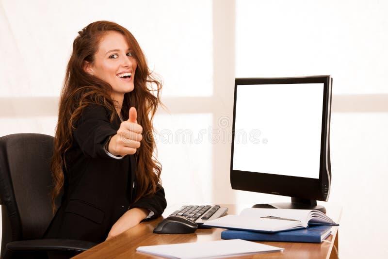 Ung tumme för show för framgång för gest för affärskvinna upp på hennes skrivbord I royaltyfri bild