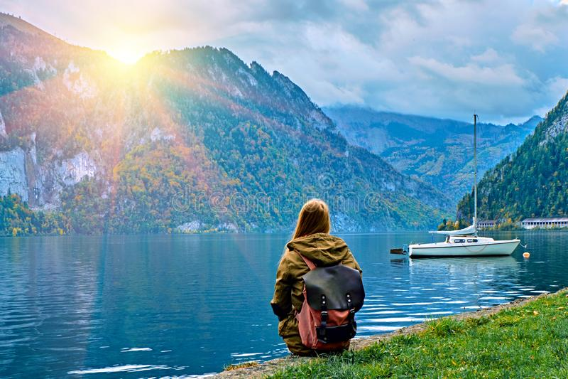 Ung turist- flicka med ryggsäcken som ser den härliga sceniska soluppgången på den österrikiska fjällängsjön Hipsterlopp arkivfoto