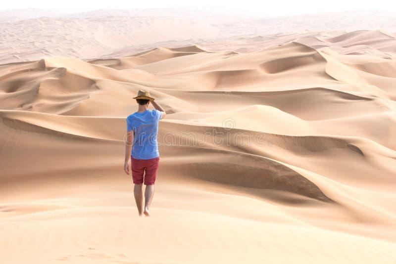 Ung turist i kortslutningar som fotvandrar i jätte- dyn arkivbild