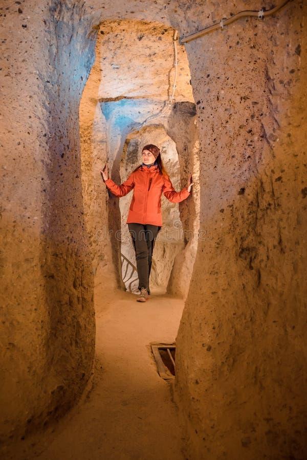 Ung turist- kvinna att undersöka den forntida Derinkuyu underjordiska grottastaden arkivfoto