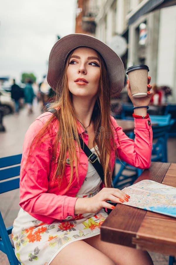 Ung turist- kvinna som har kaffe i utomhus- kafé, medan kontrollera översikten Kyla för handelsresande royaltyfri foto