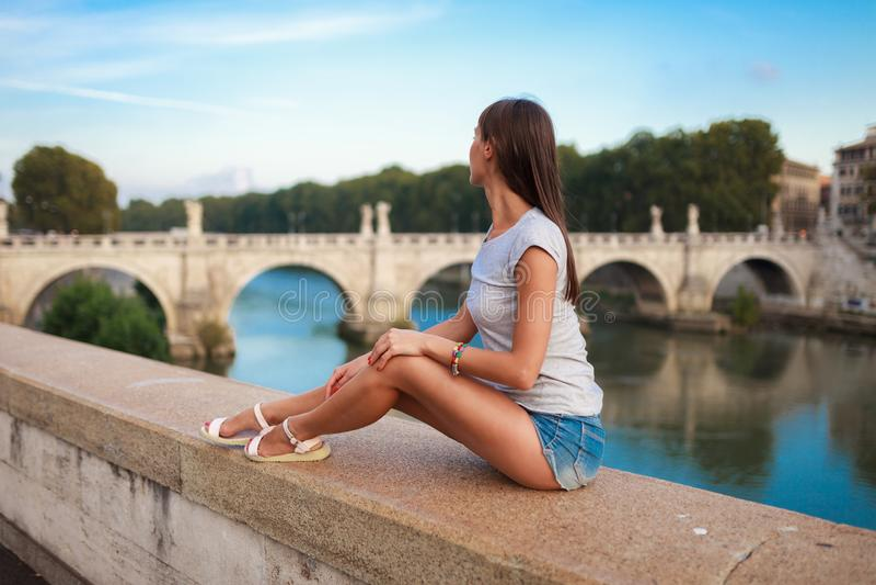 Ung turist- kvinna som sitter p? den forntida invallningen Tiber i Roma p? solnedg?ngen N?ra av bron och slotten av ?nglar angelo royaltyfria foton