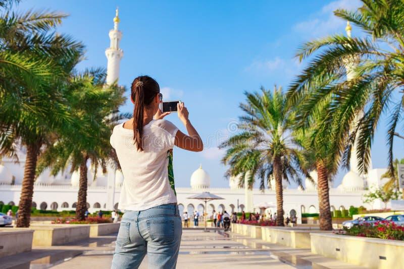 Ung turist- kvinnaskytte p? mobiltelefonSheikh Zayed den stora vita mosk?n i Abu Dhabi, F?renade Arabemiraten, Persiska viken UAE royaltyfri fotografi