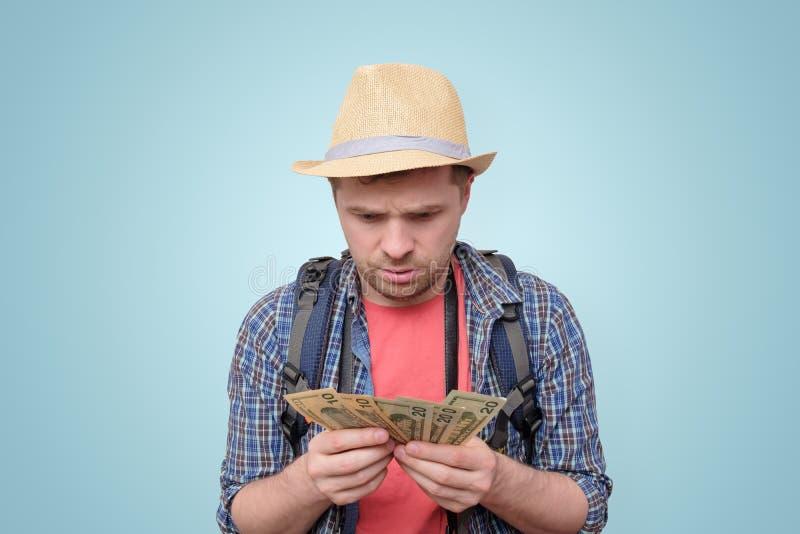 Ung turist- man i sommarhatten som rymmer dollar royaltyfri bild
