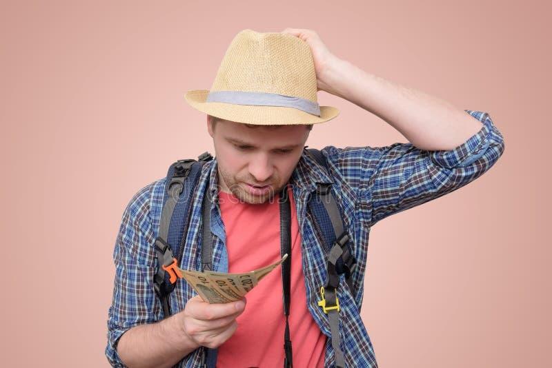 Ung turist- man i sommarhatten som rymmer dollar royaltyfria bilder