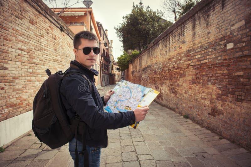 Ung turist- man som går med en översikt på den gamla stadsgatan royaltyfria foton