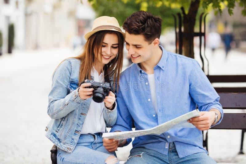 Ung turist- parresande på att le för ferier som utomhus är lyckligt Caucasian familj med stadsöversikten i sökande av dragningar  royaltyfria foton