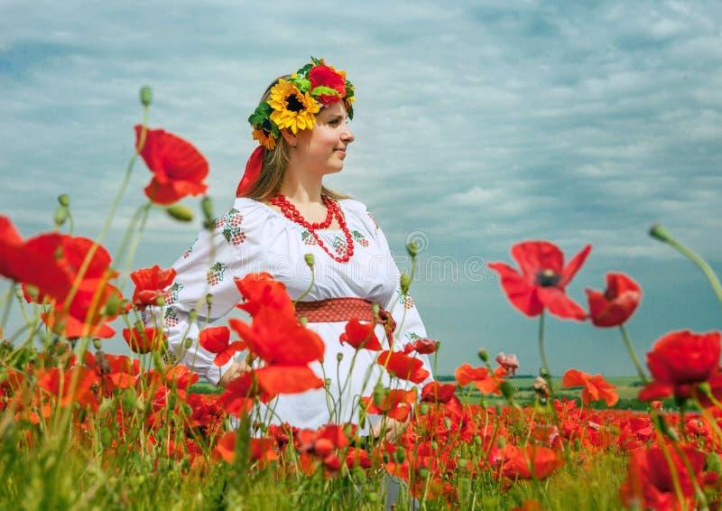Ung ukrainsk kvinna på fältet av vallmo arkivbild