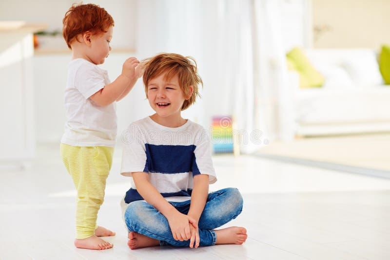 Ung unge som tolererar en yngre broderlek med hans hår royaltyfria foton