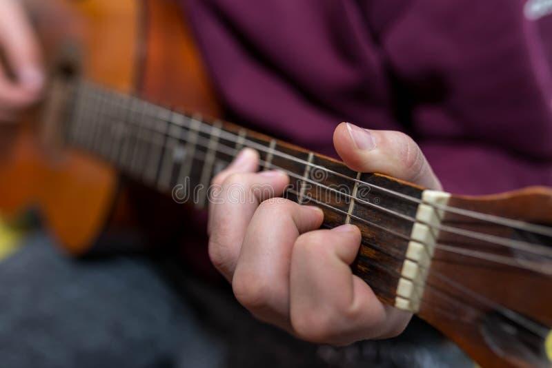 Ung unidentifiable musiker som spelar på gitarren royaltyfria bilder