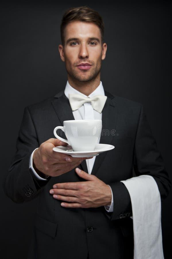 Ung uppassare i varmt kaffe för enhetlig portion royaltyfria foton