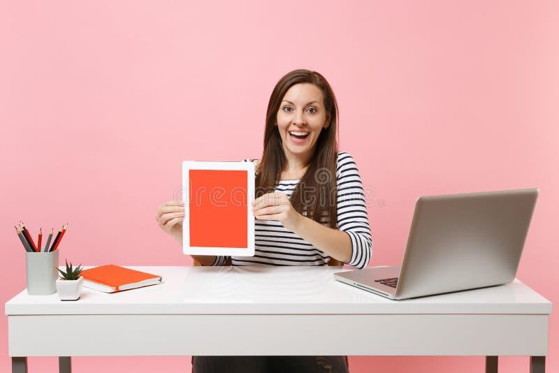 Ung upphetsad dator för kvinnahållminnestavla med den tomma tomma skärmen att sitta arbete på det vita skrivbordet med den modern arkivbilder