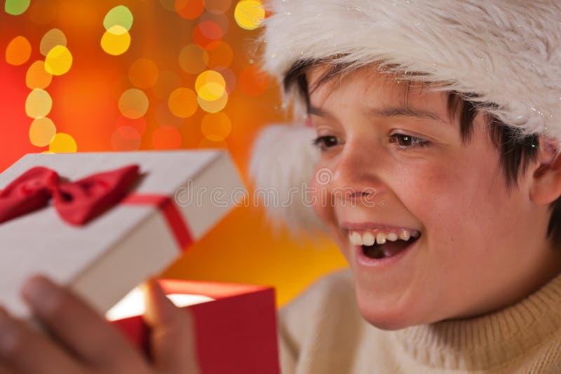 Ung upphetsad tonåringpojke som öppnar hans julgåva arkivfoton