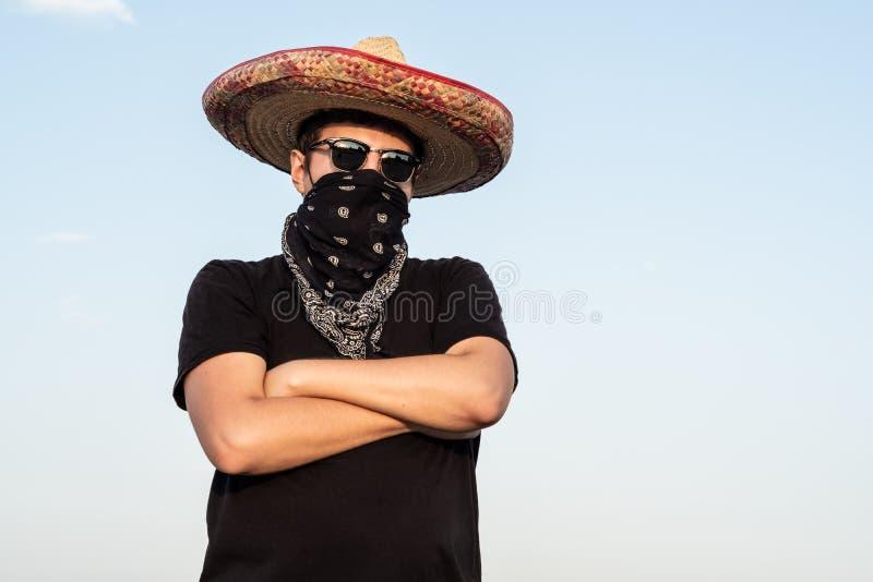 Ung uppklädd för manlig person som gangster i traditionell sombrero arkivfoto