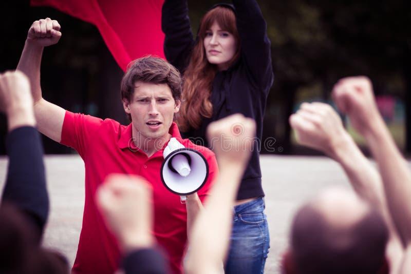 Ung upprorisk man med megafonen royaltyfri foto