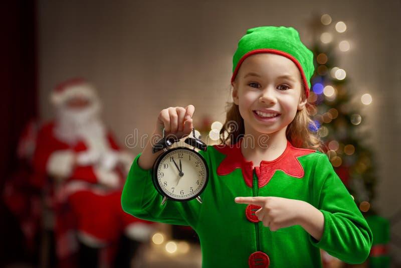 Ung ursnygg kvinna som julälva på guld- bakgrund med den tomma snirkeln arkivfoton
