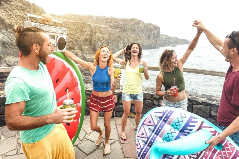 Ung vänsemesterfirare som har gyckel på den naturliga pölen på loppläge - lyckligt millenial folk som dansar och dricker coctaila arkivfoto