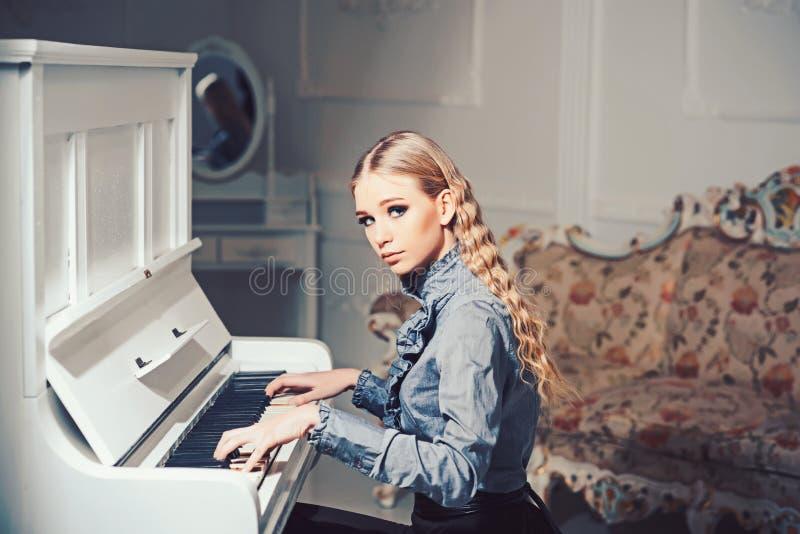 Ung viktoriansk dam i en mjuk blå klänning som spelar pianot Älskvärd blond kvinna som sitter i rum med tappningmöblemang arkivfoton