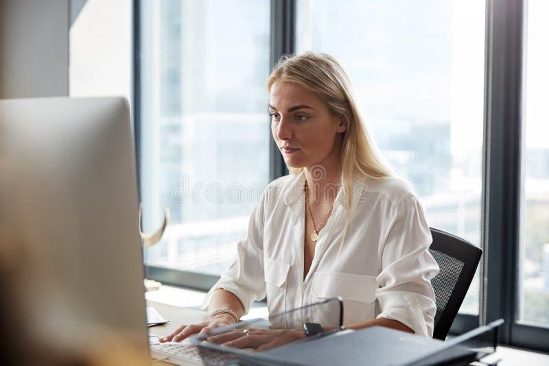 Ung vit blond kvinna som sitter på ett skrivbord som arbetar på en dator i ett idérikt kontor, slut upp royaltyfri fotografi