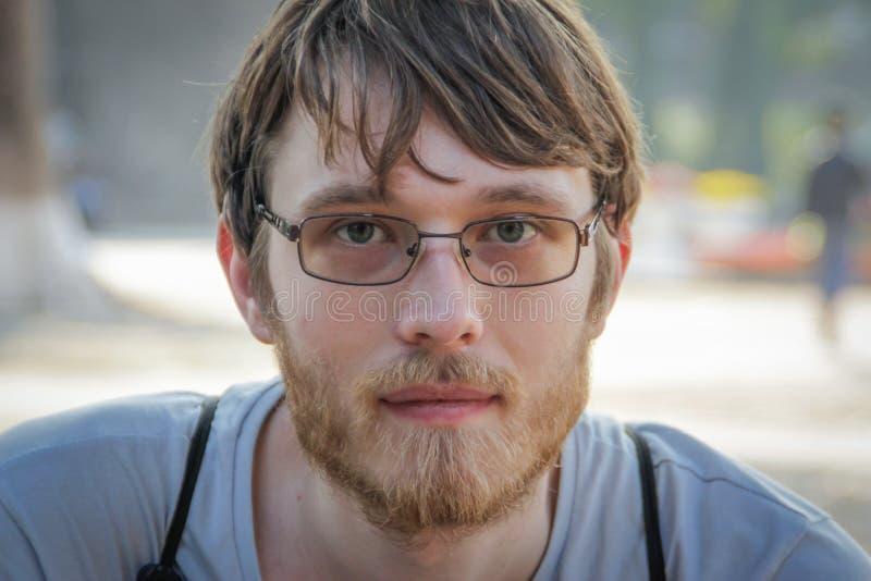 Ung vit Caucasian man som är blond med en smäll och ett skägg med exponeringsglas arkivfoton
