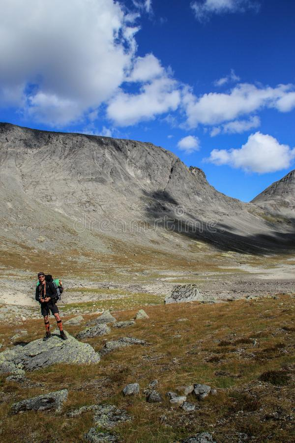 Ung vit Caucasian manlig turist med ryggsäcken mot bakgrunden av berg och klar blå himmel med moln i Karelia arkivfoto