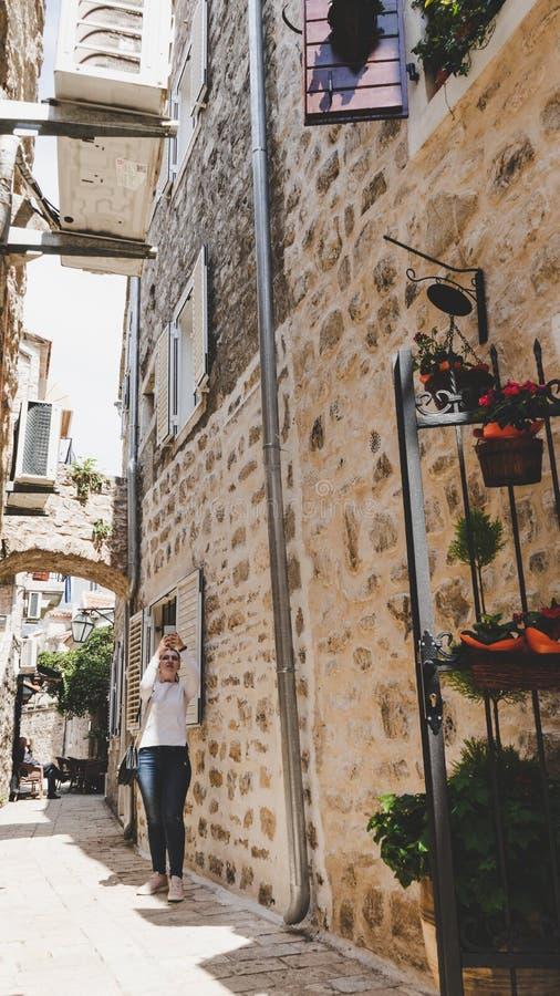 Ung vit flicka som tar bilder i de lilla smala gatorna av den gamla staden av Budva, Montenegro Kvinna som går mellan medeltida arkivbild