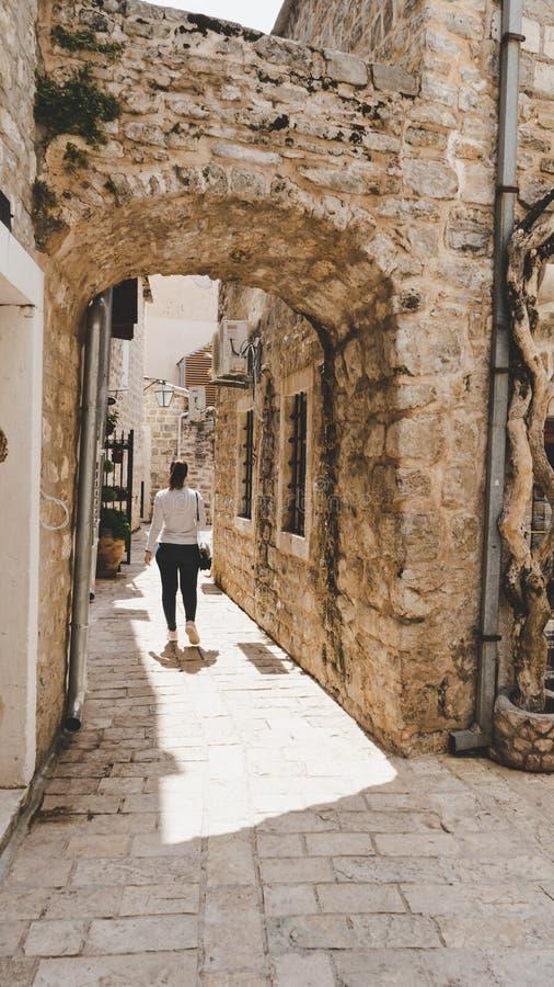 Ung vit flicka som tar bilder i de lilla smala gatorna av den gamla staden av Budva, Montenegro Kvinna som går mellan medeltida arkivbilder