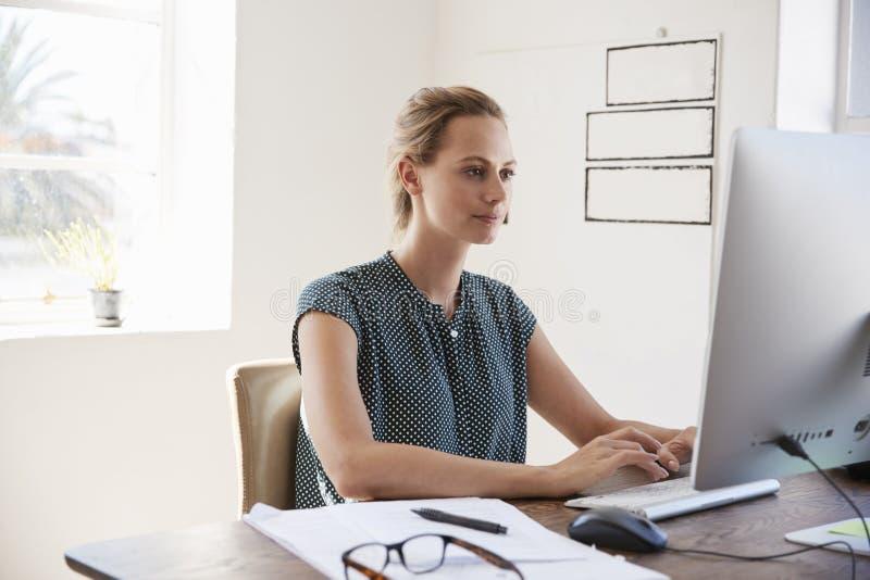 Ung vit kvinna som i regeringsställning arbetar genom att använda upp datoren, slut royaltyfri bild
