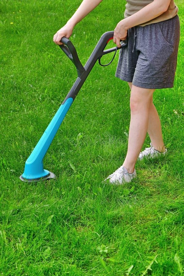 Ung vit kvinna som rymmer en bunden med rep gräsbeskärare fotografering för bildbyråer